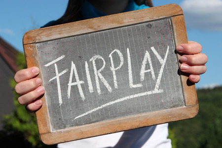 FAIRPLAY written with chalk on slate shown by young female Imagens