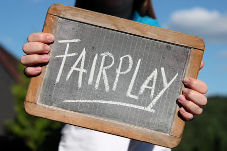 FAIRPLAY written with chalk on slate shown by young female Stock Photo