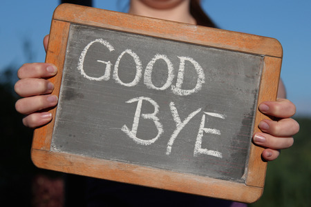 good bye: GOOD BYE written with chalk on slate shown by young female Stock Photo