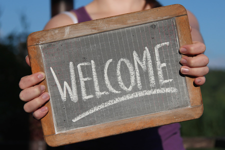 shown: WELCOME written with chalk on slate shown by young female Stock Photo