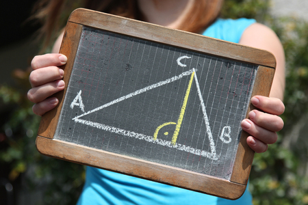 theorem: geometric triangle sketched with chalk on slate shown by young female Stock Photo