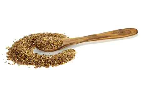 herbolaria: cuchara de madera con grano para moler semillas de lino aislado en el fondo blanco