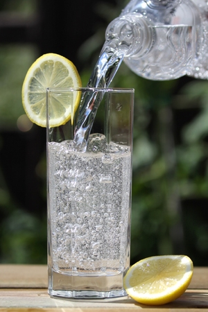 sparkling water: sparkling water pouring into glass Stock Photo