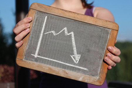 downward graph sketched with chalk on slate shown by young female