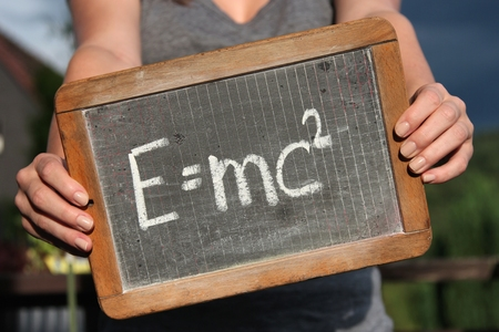 equivalence: theory of relativity written with chalk on slate shown by young female