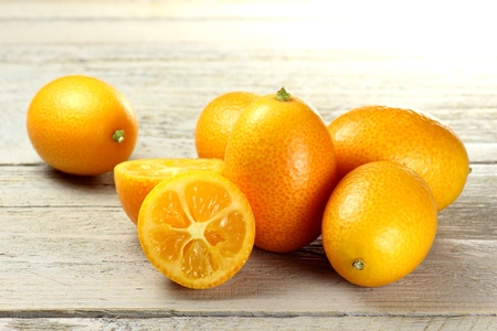 mellowness: kumquats isolated on wooden background