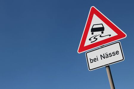 when: German road sign: slippery road when wet