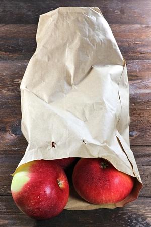apple paper bag: apples (variety Elstar) in a paper bag on wooden background