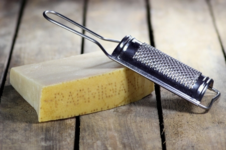 ripeness: Italian hard cheese with grater on wooden background Stock Photo