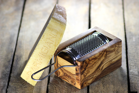hard cheese: Italian hard cheese with grater on wooden background Stock Photo