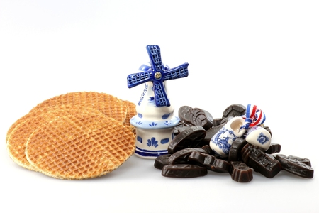 delftware: traditional dutch syrup waffles and licorice candies with delftware isolated on white background