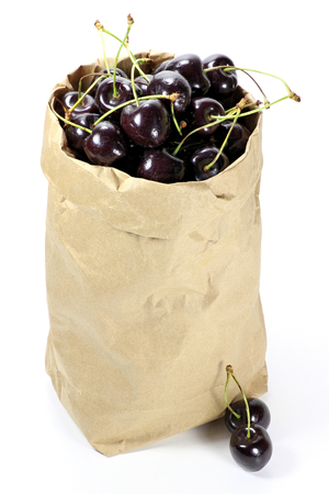mellowness: cherries in paper bag isolated on white background Stock Photo