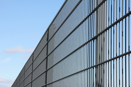 perimeter: welded wire mesh fence against blue sky