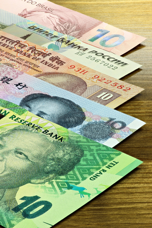 emerging markets: banknotes of the BRICS states on wooden background