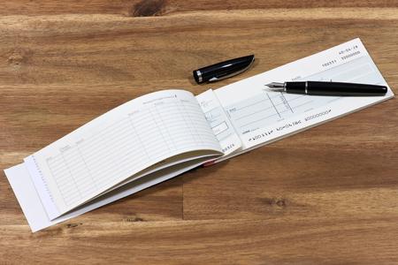 Britse chequeboek op houten bureaublad (rekeningnummer is digitaal veranderd en niet echt)