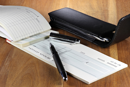 British checkbook on wooden desktop (account number is digitally altered and not real)