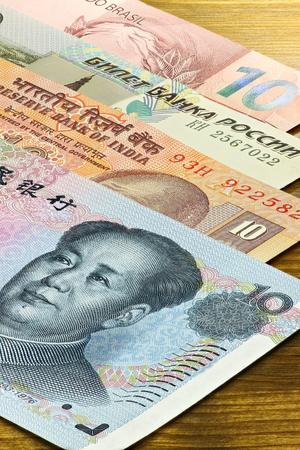 emerging markets: banknotes of the BRIC states on wooden background Stock Photo