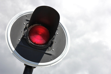 red traffic light against cloudy sky
