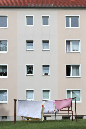 rent index: clothesline with bedding in front of an apartment block