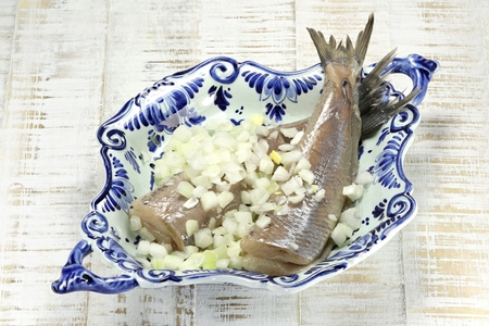 delftware: soused herring in delftware bowl on wooden background Stock Photo