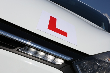 affixed: magnetic British L-plate affixed to the front of a white car Stock Photo