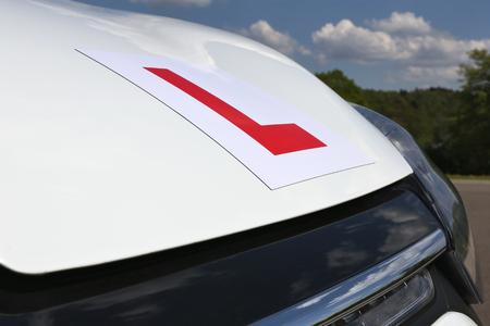 magnetische Britse L-plaat aangebracht op de voorkant van een witte auto