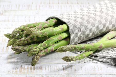 mellowness: bundle of green asparagus on wooden background