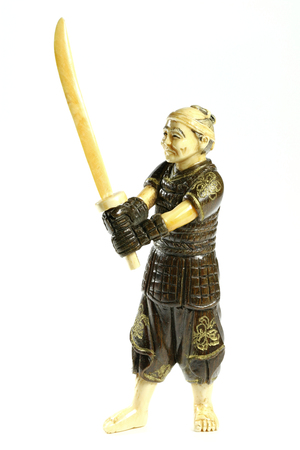 counterbalance: antique Japanese netsuke warrior made of ivory and boxwood isolated on white background