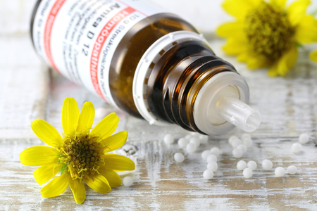 pseudoscience: scattered homeopathic arnica pills on wooden background