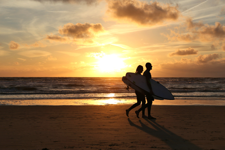 surfers: two surfers walking on a beach at sunset
