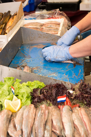 weekly market: traditional soused herring being prepared and Offered at Dutch weekly market