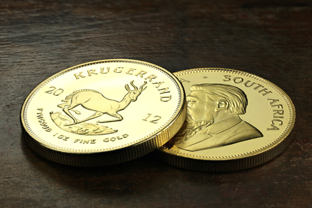 an ounce: South African 1 ounce gold bullion coins on wooden background