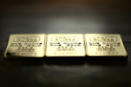 ounce: three 1 ounce gold ingots on wooden background