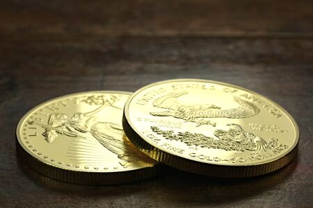 ounce: 1 ounce American gold eagle bullion coins on wooden background Stock Photo