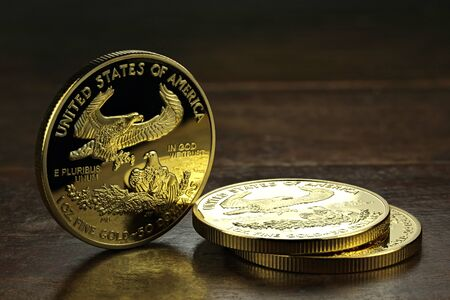 an ounce: 1 ounce American gold eagle bullion coins on wooden background Stock Photo