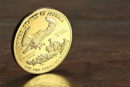 ounce: 1 ounce American gold eagle bullion coin on wooden background Stock Photo