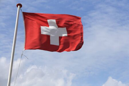 flagstaff: Swiss flag blowing in the wind Stock Photo