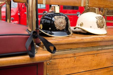 voiture de pompiers: deux casques de pompier vieux à bord d'un moteur de feu classique Banque d'images