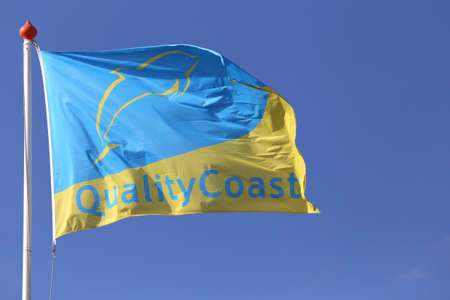 sustainable tourism: QualityCoast flag blowing in the wind Editorial