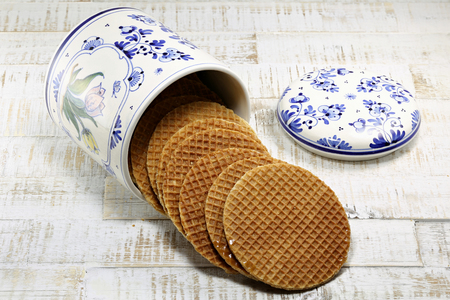 treacle: traditional Dutch syrup waffles in original Delftware container on wooden background