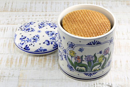 delftware: traditional Dutch syrup waffles in original Delftware container on wooden background