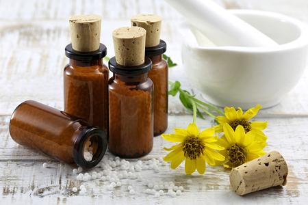 Píldoras homeopáticas de árnica dispersos en el fondo de madera Foto de archivo - 64140750