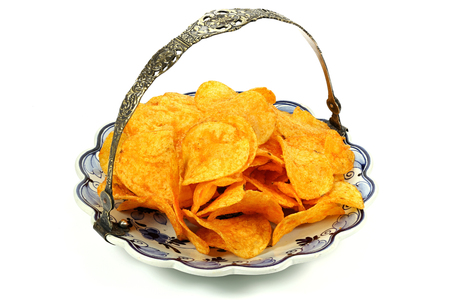 paprika flavored potato chips served on delftware plate isolated on white background