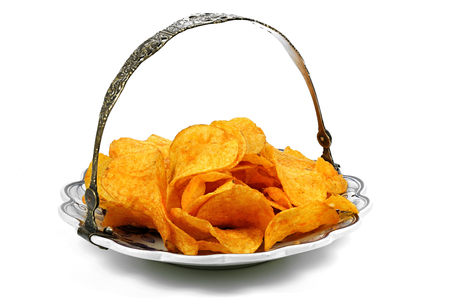 grasp: paprika flavored potato chips served on delftware plate isolated on white background