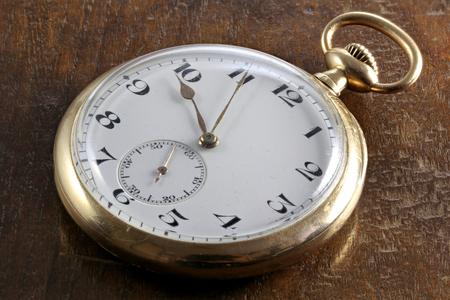 14k: antique Swiss 14k gold pocket watch on wooden background