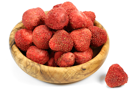 freeze-dried strawberries in a wooden bowl isolated on white background