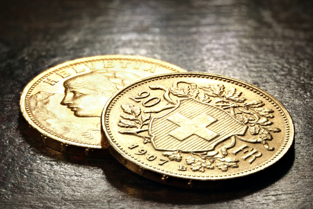 Swiss Vreneli gold coins on rustic wooden background 写真素材