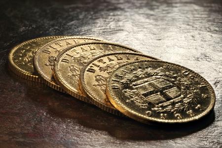 Italian Victor Emmanuel II gold coins on rustic wooden background Imagens