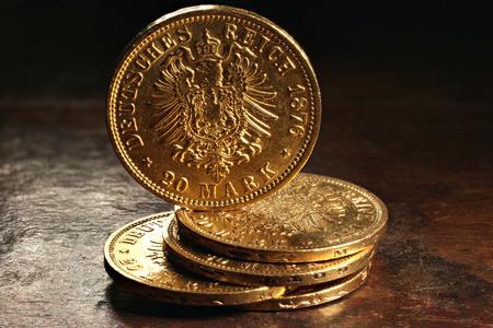 Hamburg gold coins (German Empire Goldmark) on rustic wooden background