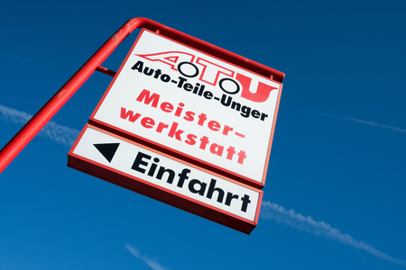 approximately: ATU signpost against blue sky. ATU is a large car repair shop chain and retailer for car components with approximately 600 branches in Germany, Austria and Switzerland. Editorial